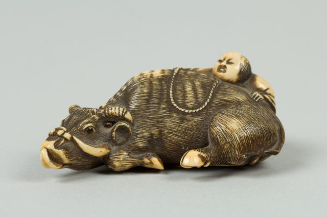 Netsuke of Boy Climbing over the Back of a Cow