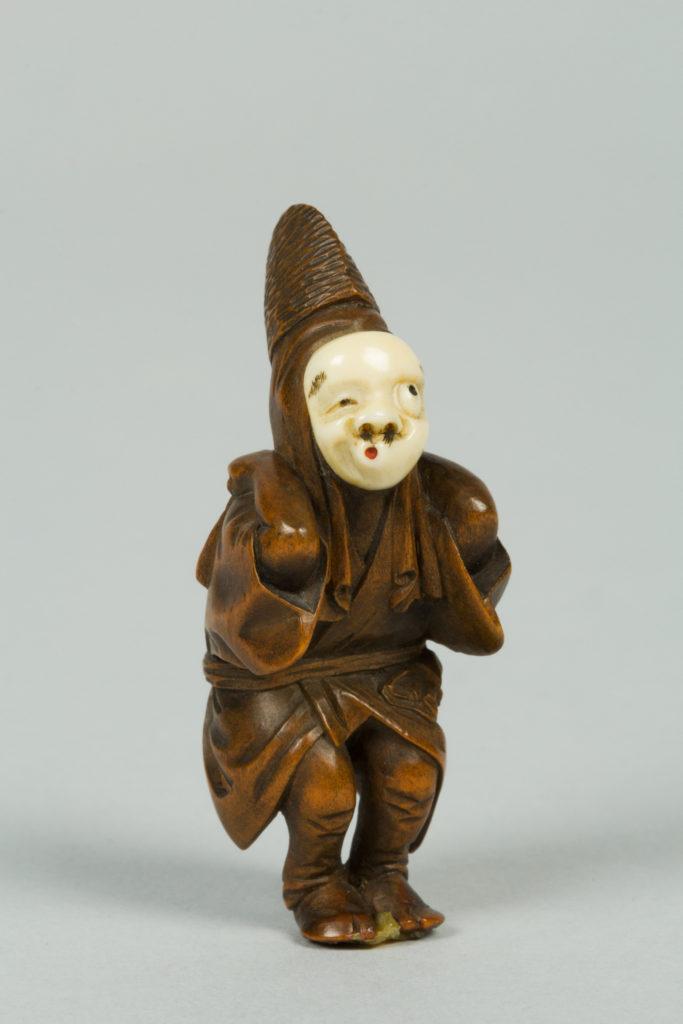 Netsuke of Boy Wearing an Ivory Mask