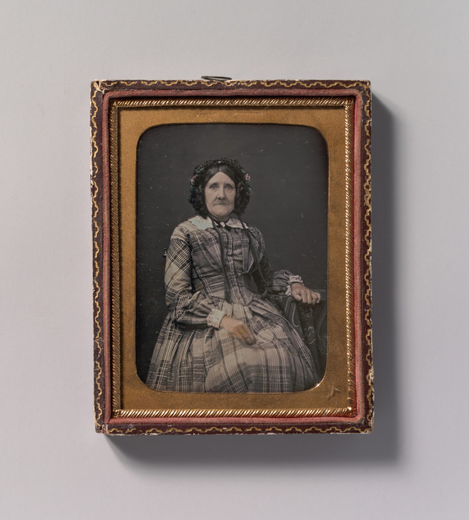 [Seated Elderly Woman Wearing Plaid Dress and Bonnet]