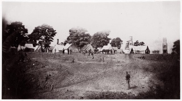 [Unidentified camp with ruined chimneys in background].  Brady album, p. 130