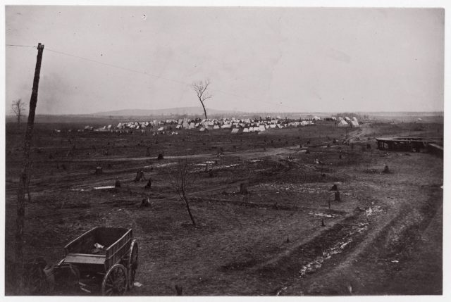 [Wagon in a landscape with army encampment in the distance].  Brady album, p. 125