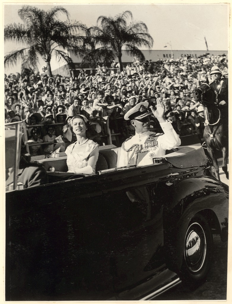 [Her Majesty Queen Elizabeth the Second and His Royal Highness The Duke of Edinburgh, seated in open top car, being driven through a street lined with crowds of people,1954]