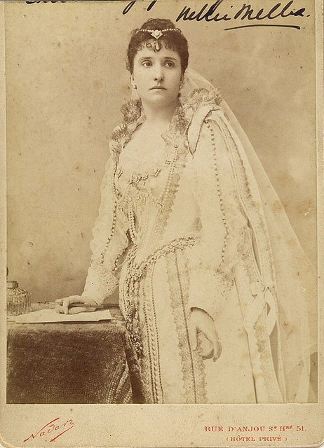 "Nellie Melba, in costume for ""Lucia di Lammermoor"", posed to sign the marriage certificate, ca. 1888 / photographer Felix Nadar, rue d'Anjou, St. Honore, 51, Paris"