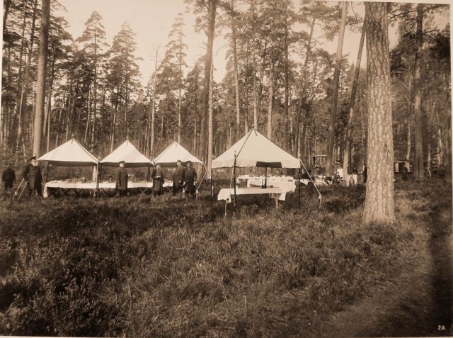 Cooks and servants preparing dinner in the forest for hunting participants - members of the imperial family and guests.