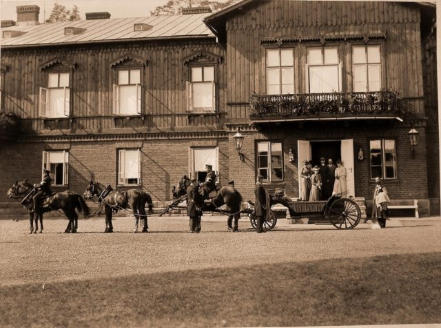 Empress Maria Feodorovna and others at the entrance to the hunting lodge.