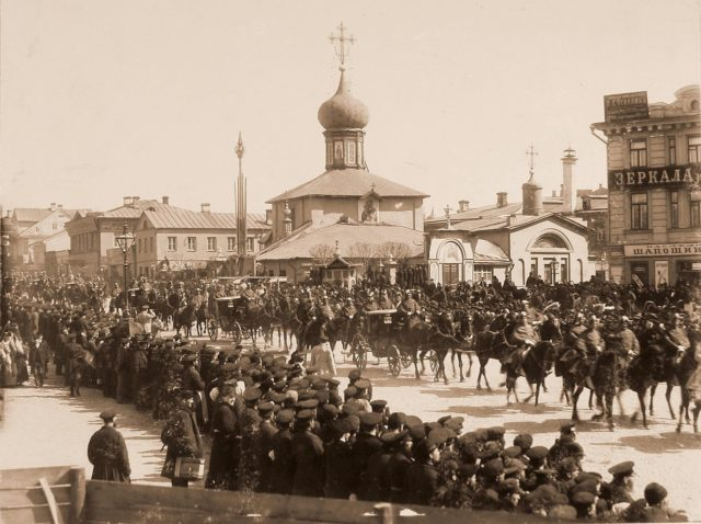 Crews and carriages with palace ranks pass the church of Grebnevskaya Mother of God