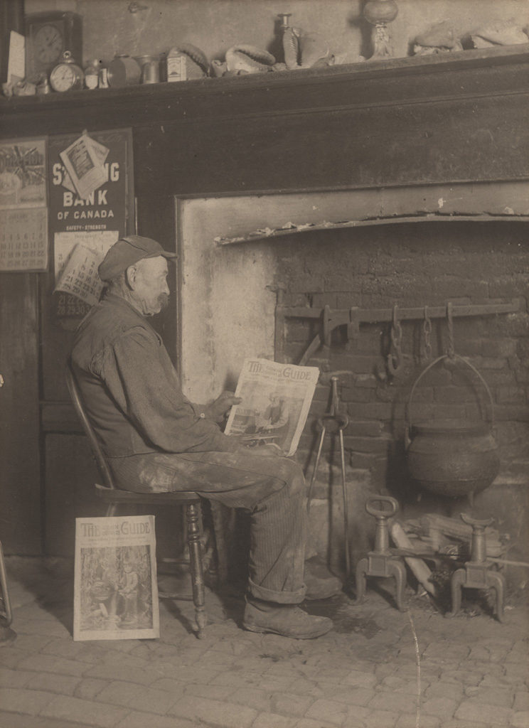 Man reading by fireplace, 1900