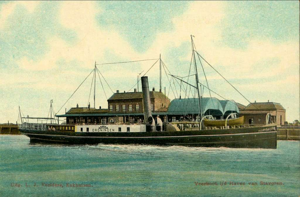 """HUA-162040-Afbeelding van het stoomschip """"Groningen"""" voor de bootdienst Enkhuizen-Stavoren in de haven van Stavoren. Op de achtergrond het H.S.M.-station Stavoren"""