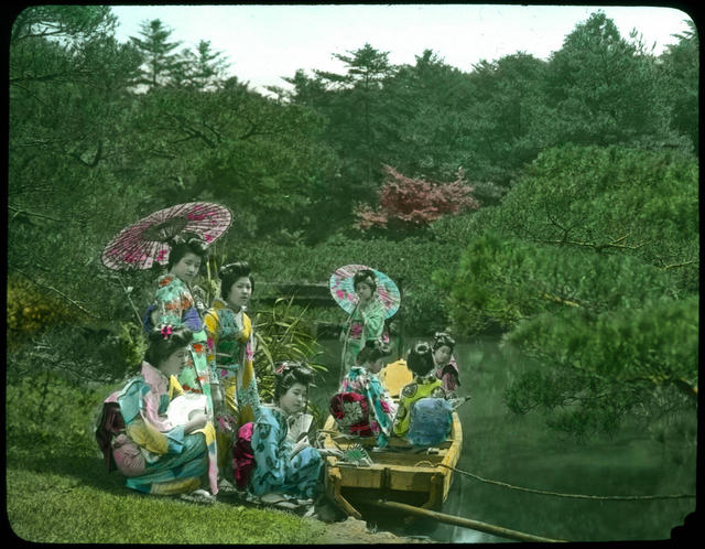 Eight young women in Kimonos, four in wooden boat on water, four on bank beside boat, two of them holding open parasols.