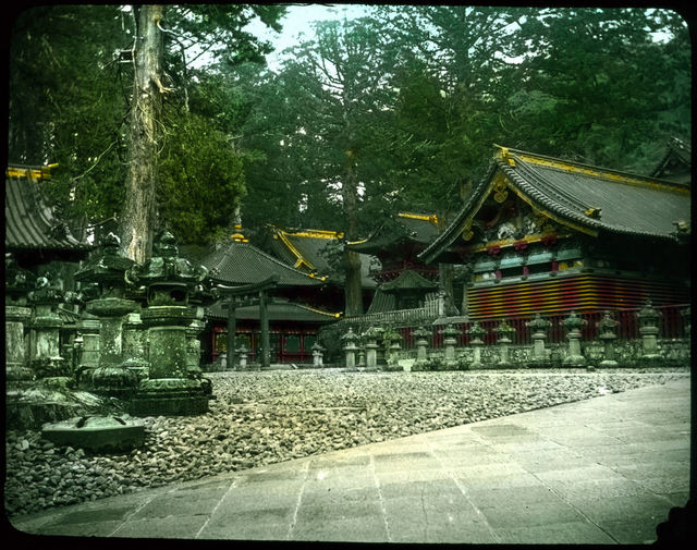 Group of buildings set among trees; ornamental stone wall in front.