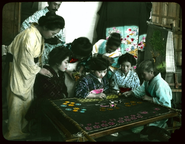 Group of women and one man watching young woman working on large embroidery.