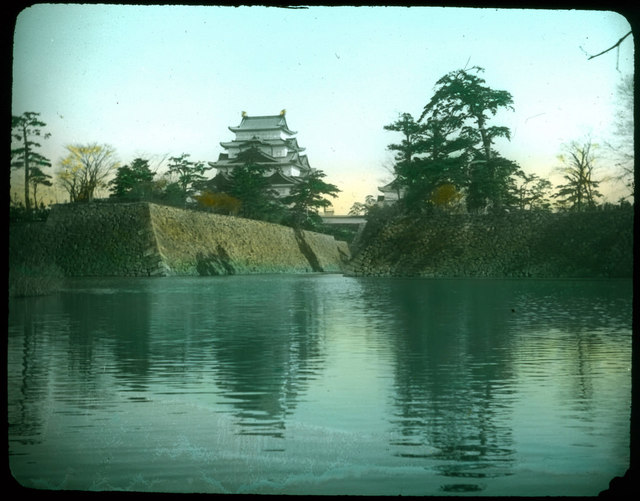 High stone embankments above river; line of trees on top of each embankments; tall building with temple roofs on one side; another building hidden behind trees on other side.