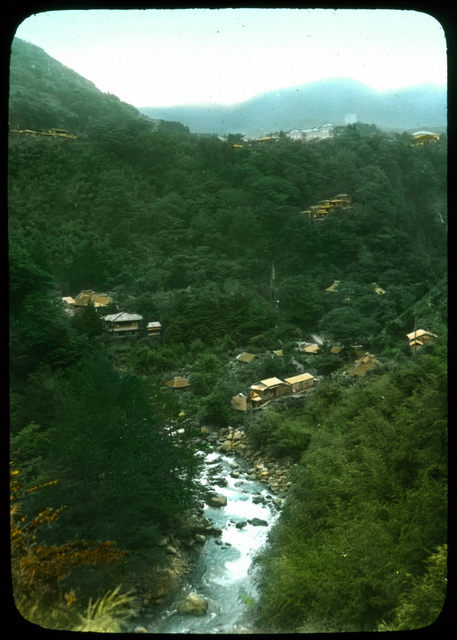 Houses in the woods, river in foreground.