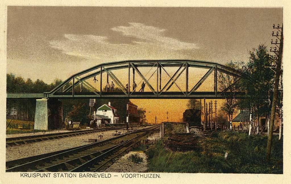HUA-165079-Gezicht op het spoorviaduct van de spoorlijn Nijkerk - Ede over de spoorlijn Amersfoort - Apeldoorn te Barneveld (Barneveld Kruispunt), met op de achtergrond het H.S.M.-station Barneveld-Voorthuizen e