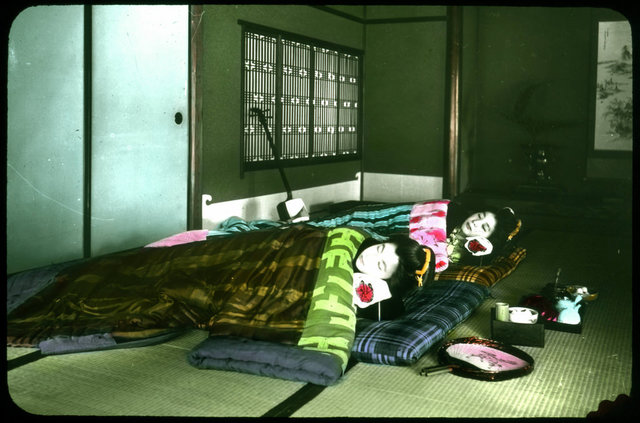 Interior shot of two geishas asleep in bedding on floor mats; musical instrument, fan and implements for tea ceremony nearby.