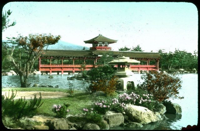Long red wooden covered bridge with ornamental roof; woods on either side of bridge, woods and mountain behind; water and landscaped point of land with flowers in foreground.