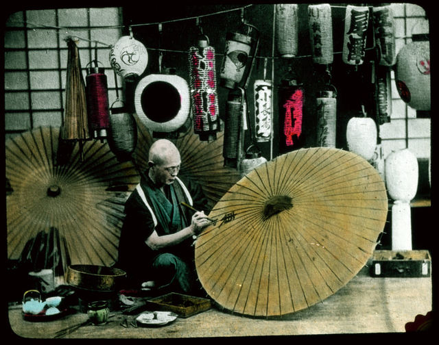 Man painting parasols; painted lanterns in background.