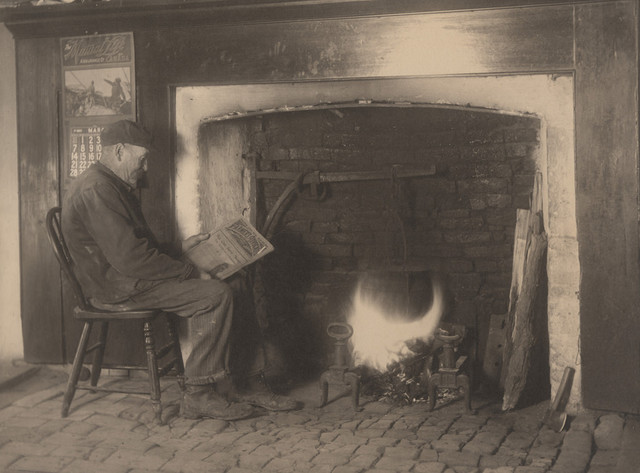 Man reading by fire, date unknown