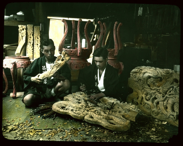 Men carving wooden furniture of intricate design.