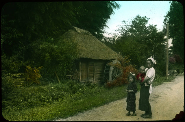 Mother and children outside rural hut with waterwheel.