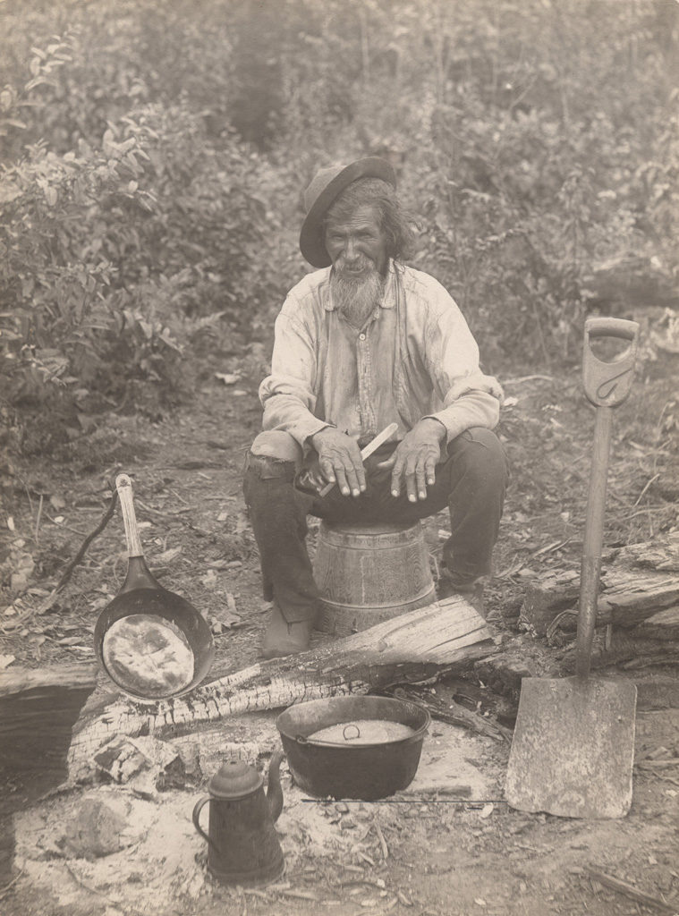 Old man cooking outdoors, 1910
