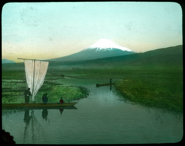 People in boats on waterways through rice fields; snow-covered mountain in background.