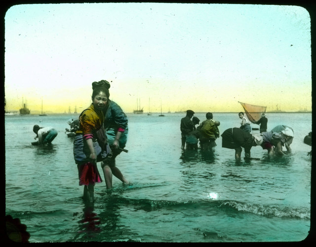 People wading in sea; fisher with hand net; boats in background.