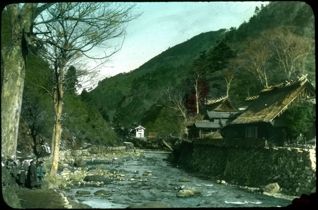 River in mountains; raised bank with houses on one side; Japanese children on side of river.