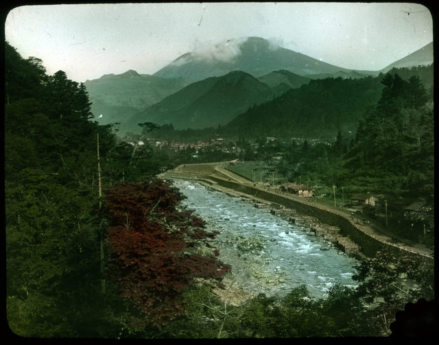 River with manmade embankment and road on one side; line of buildings along embankment; forest on other side of river, town and mountains in background.