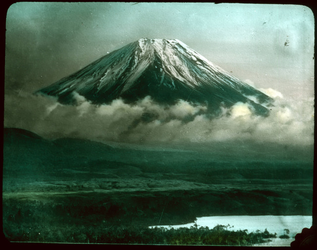 Snow-covered mountain (Mt. Fuji?) wreathed with clouds; low ground leading down to water in foreground.