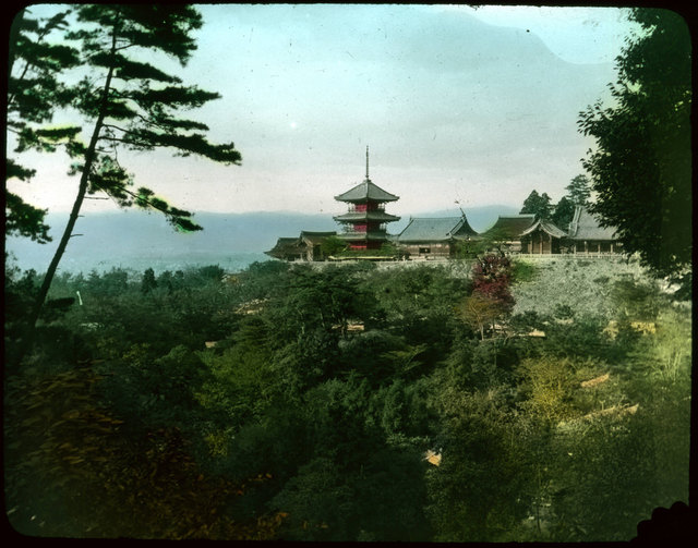 Temple and houses on hill over valley filled with trees.