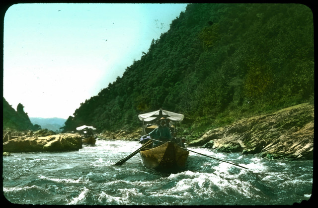 Two boats with cloth canopies being rowed along river; wooded mountain on one side; rushing water in foreground.