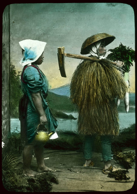 Two people in costume posing in front of painted backdrop - one in grass coat and hat, carrying farm implement over shoulder and holding vegetables; the other, a woman in a blue dress with a red (over mantel), legs bare to the knees, wearing a white kerch