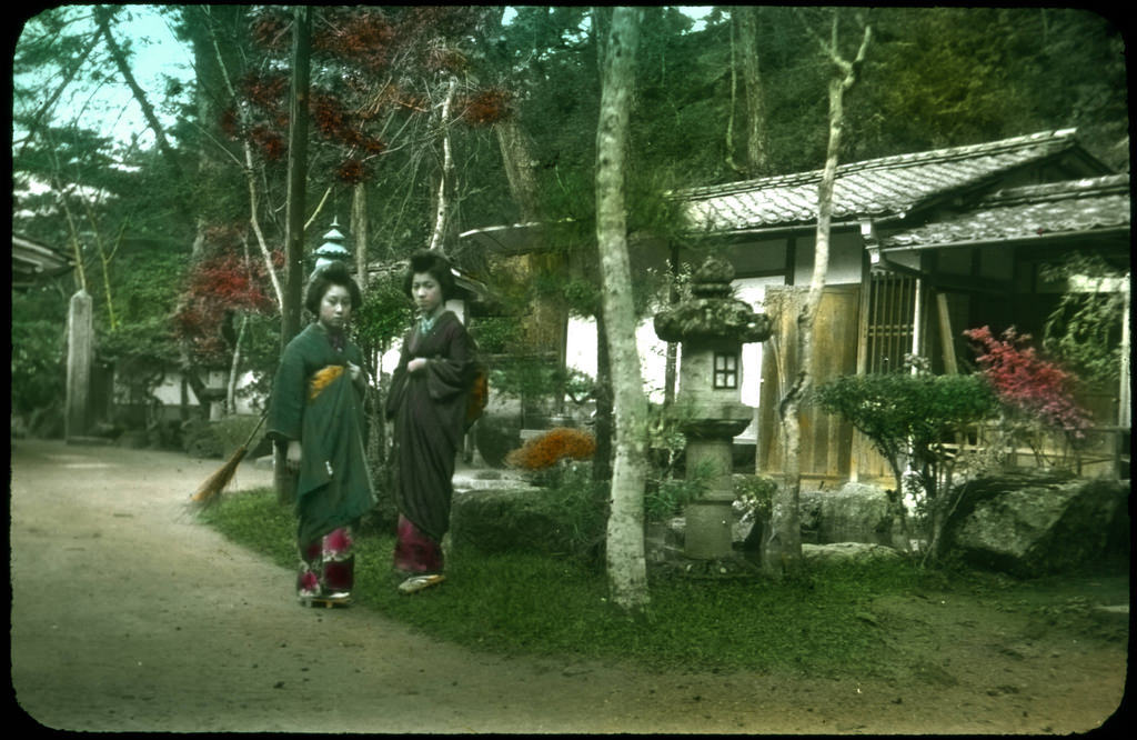 Two women in traditional dress posing outside house in tiny ornamental garden.