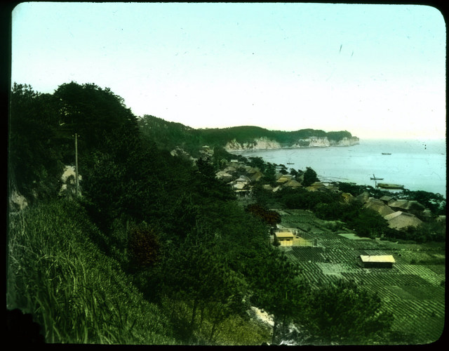 Village on a bay; fields and hillside in foreground.