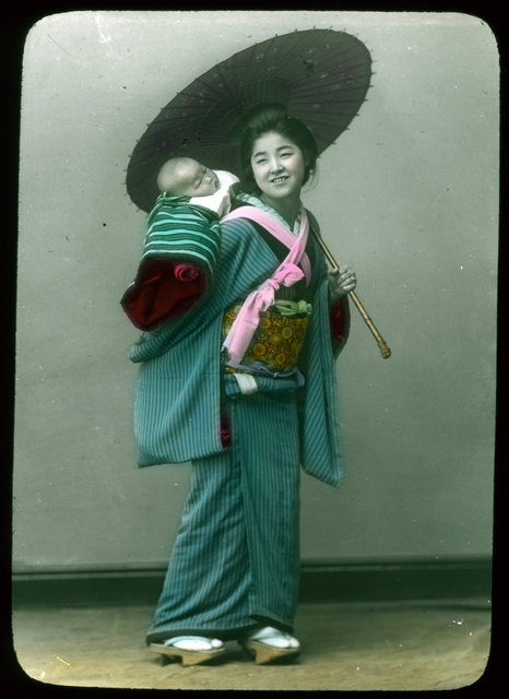 Woman in traditional dress holding open parasol and carrying baby on her back.