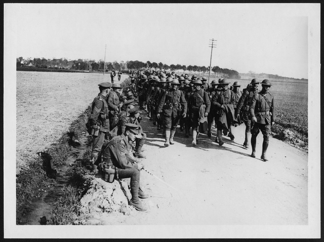 American troops in France passing British men resting by the roadside