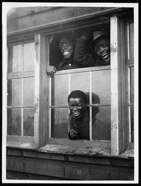 At the window of one of their huts