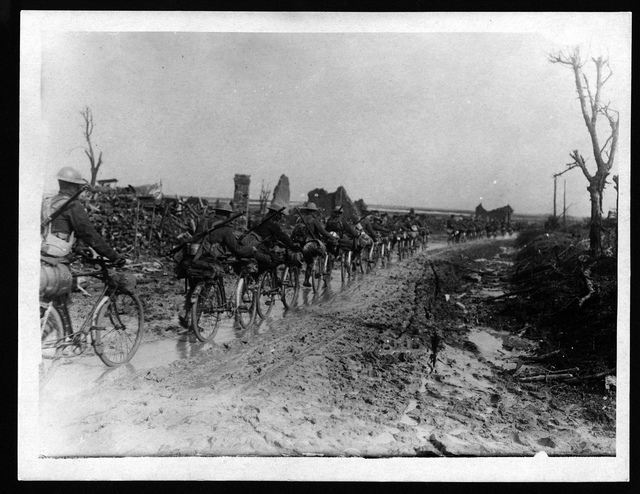 Cyclist scouts travelling along a road, France, during World War I