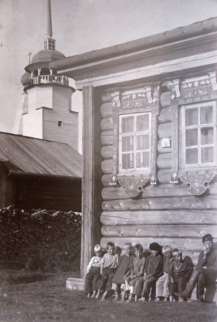 Kids sitting next to the house. Onega, Arkhangelsk region, Russia, White Sea.