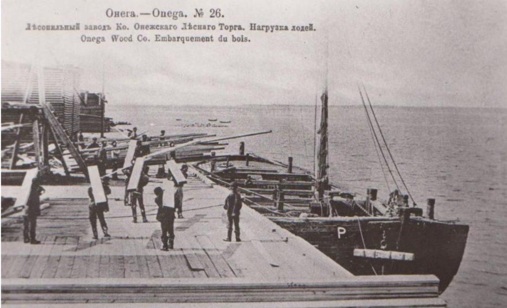 Loading wood on barges. Onega Pier, Arkhangelsk region, Russia, White Sea.