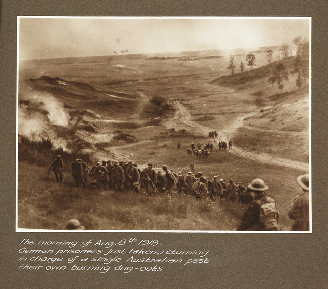 The morning of Aug.8th 1918. German prisoners just taken, returning in charge of a single Australian past their own burning dug-outs