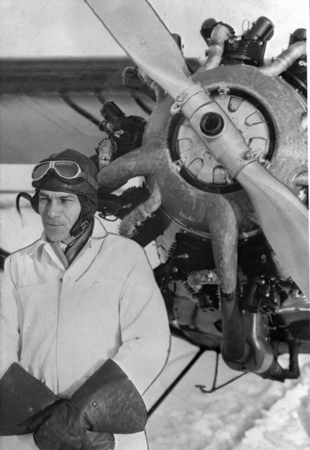 Bush pilot Charles (Cy) Becker standing in front of airplane