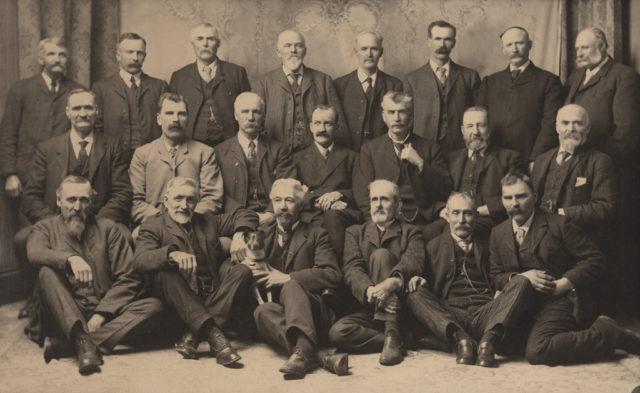 Group portrait of men plus dog, date unknown