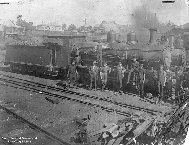 Railway workers standing beside a steam locomotive at Roma Street, Brisbane, 1919-1920 (4732516656)