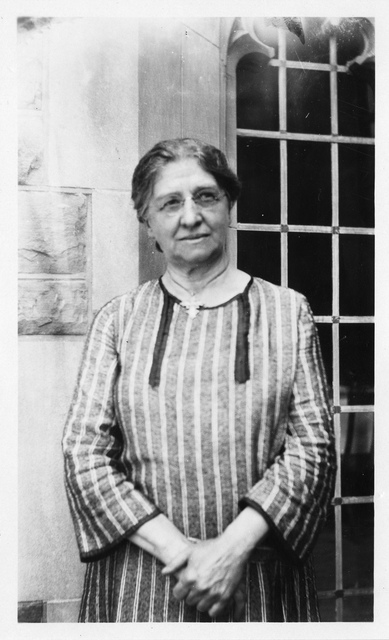 Carrie M. Derick (1862-1941), standing outside building