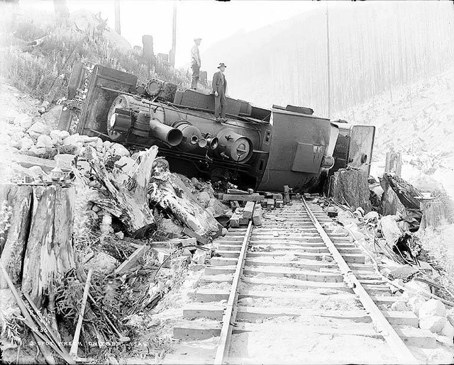 Two men standing atop wrecked locomotive on the Great Northern Railway tracks