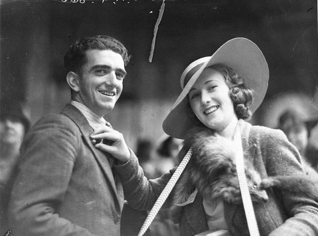A United Charities worker selling a Rose Day button to a man, c. 1930s, by Sam Hood