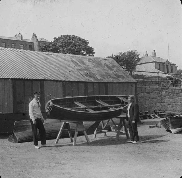 Two men pictured with rowboats in a yard - Dun Laoghaire