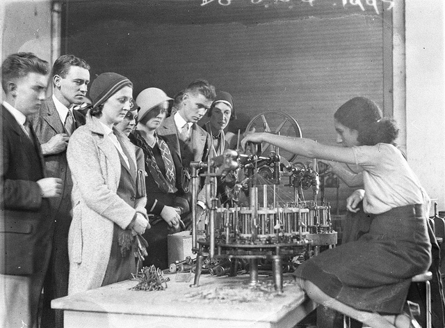 Visitors watch girl operating filament winding machine in a lamp factory, c. 1931, by Sam Hood
